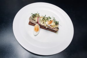 a herring fillet in sweet and sour marinade served with brown pumpkin bread, apple and red onion salad, a boiled egg, watercress and radishes