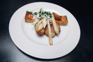 a pie with fresh spinach and shallots served with white Czech asparagus and roasted young potatoes