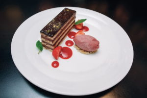 a slice of cake served with homemade rhubarb and strawberry ice-cream
