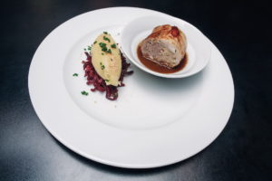 rolled pork belly filled with sauerkraut and bacon, served with potato gnocchi, beetroot cabbage and gravy