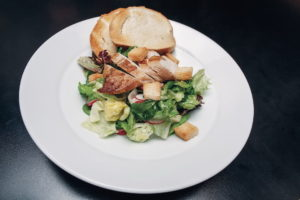 torn lettuce leaves with herb and kefir dressing, white bread croutons, radishes, roasted chicken breast with skin on, lamb's lettuce and warm crusty bread